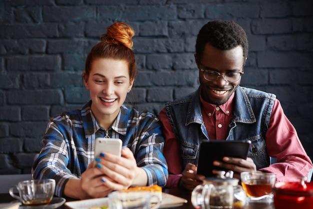 Coppia usando gadget moderni mentre ti rilassi al caffè. informazioni dai capelli rossi della lettura della donna sulla pagina web tramite telefono cellulare mentre video di sorveglianza dell'uomo di colore sulla compressa digitale Foto Gratuite