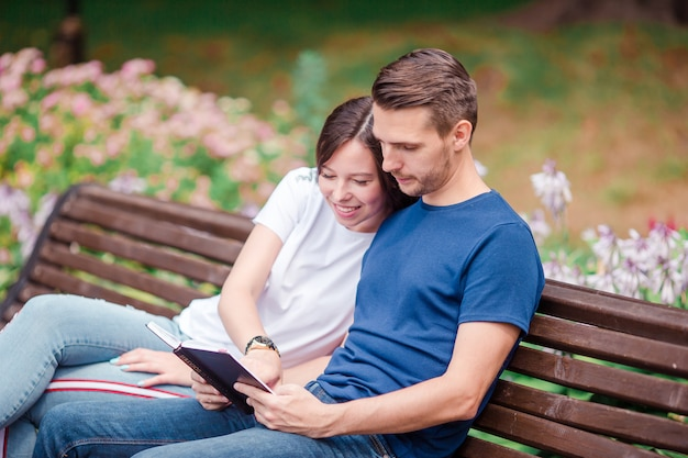 Couple using tablet and cellphone in public park. Premium Photo