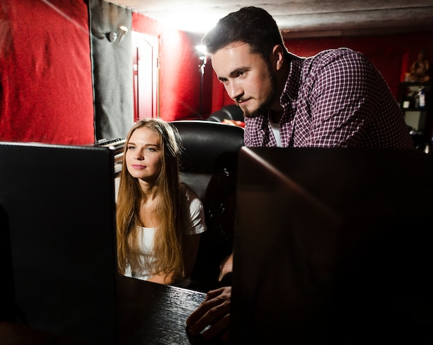 コンピューターを使用して音楽のミキシングとマスタリングを行うカップル 無料写真