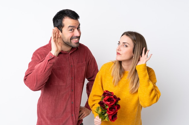 Couple in valentine day holding flowers over isolated wall listening to something by putting hand on the ear Premium Photo