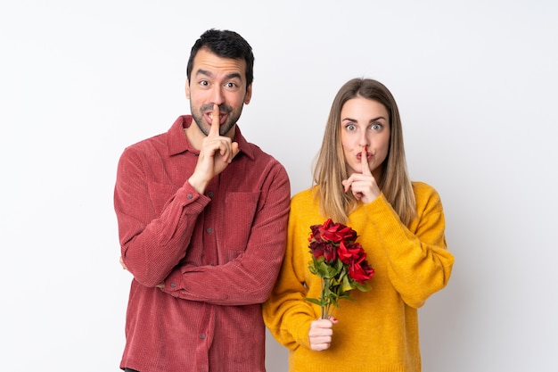 Couple in valentine day holding flowers over isolated wall showing a sign of silence gesture putting finger in mouth Premium Photo