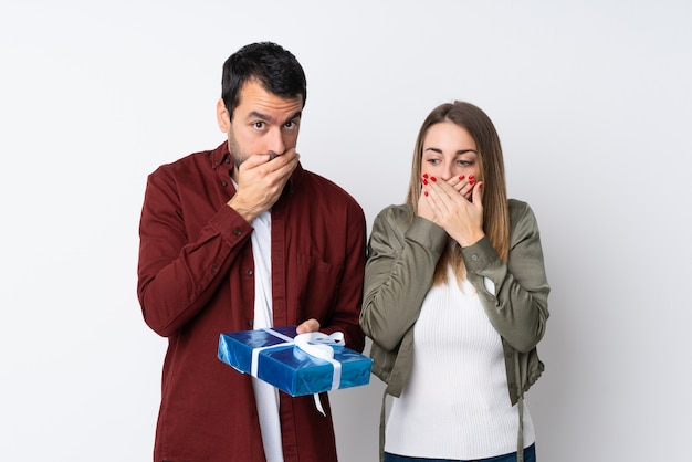 Couple in valentine day holding a gift over isolated wall covering mouth with hands Premium Photo