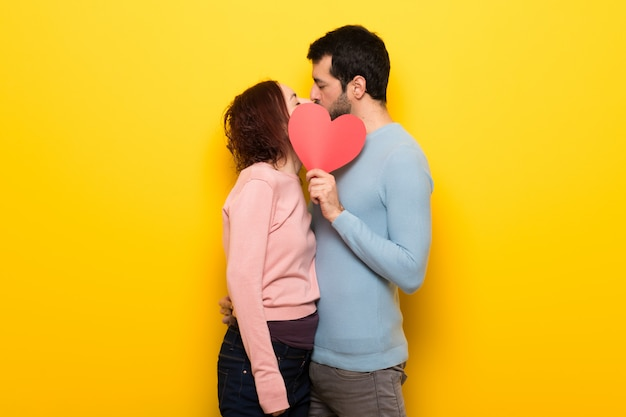 Couple in valentine day holding a heart symbol and kissing Premium Photo