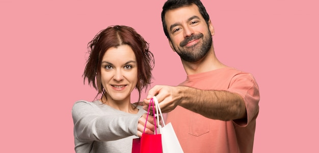 Couple in valentine day holding a lot of shopping bags over isolated pink background Premium Photo