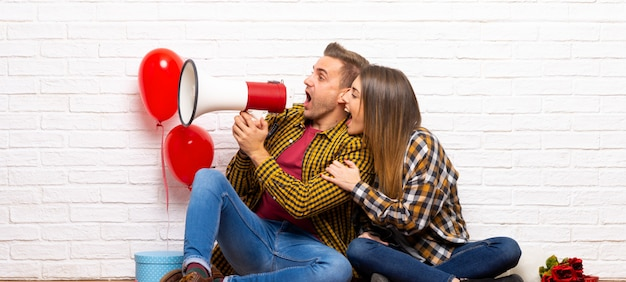 Couple in valentine day at indoors shouting through a megaphone Premium Photo