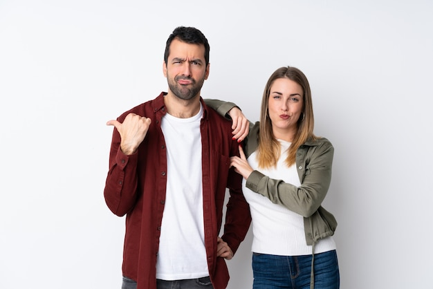 Couple in valentine day over isolated wall frustrated and pointing finger to the side Premium Photo