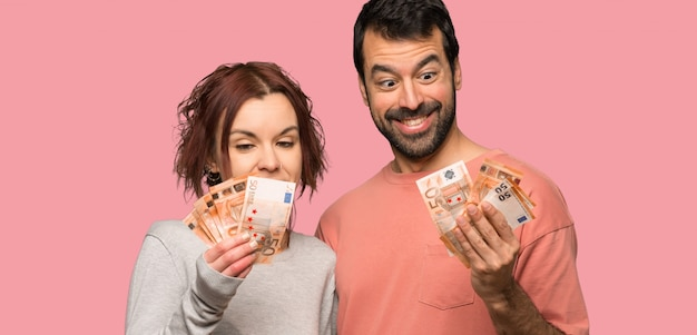 Couple in valentine day taking a lot of money over isolated pink background Premium Photo