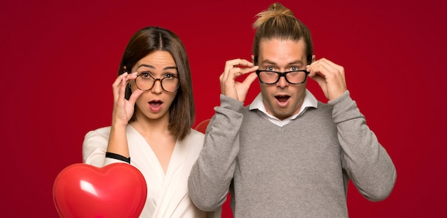 Couple in valentine day with glasses and surprised over red background Premium Photo