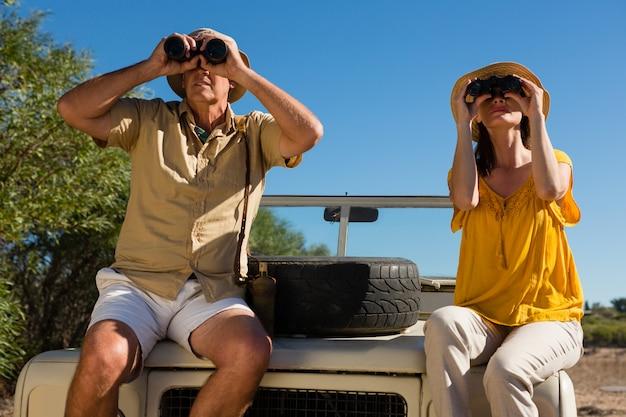 Couple in vehicle looking through binoculars while sitting on vehicle hood Free Photo