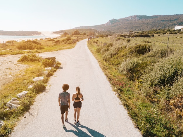 Couple walking along road between sea and hills Free Photo