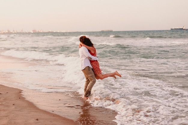 Couple walking on the beach holding hands Premium Photo