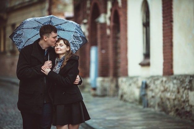 couple walking in the rain with an umbrella photo