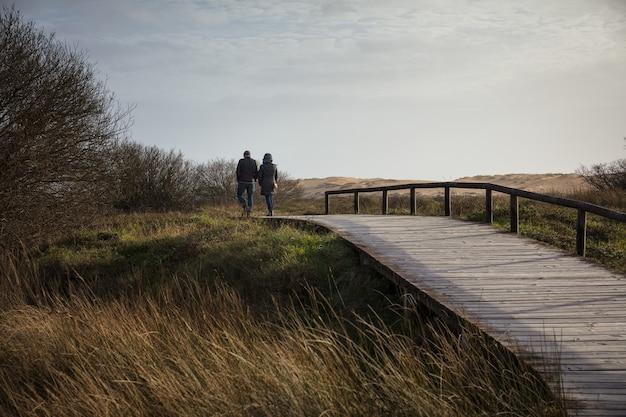 Пара идет по деревянному мосту в окружении поля и холмов под солнечным светом Бесплатные Фотографии