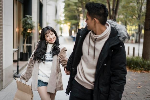 Пара гуляет по улице с сумкой для покупок Premium Фотографии