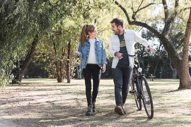 Couple walking with bike in park Premium Photo