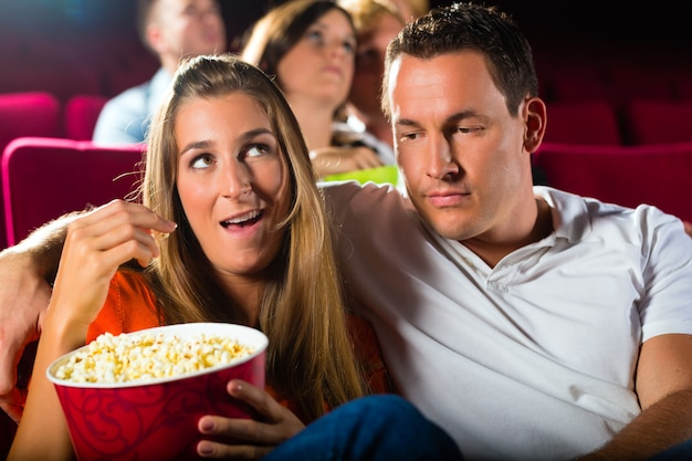 Couple watching movie at movie theater and eating popcorn Premium Photo