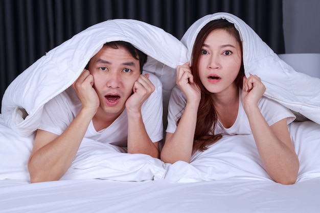 Couple watching scared movie under the blanket on bed Premium Photo
