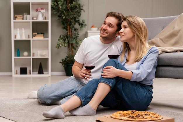 Пара смотрит телевизор и пьет вино Бесплатные Фотографии