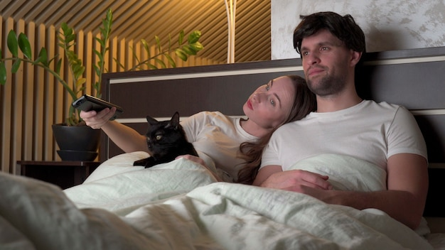 침대에 누워 집에서 밤에 Tv를 시청하는 커플. 프리미엄 사진