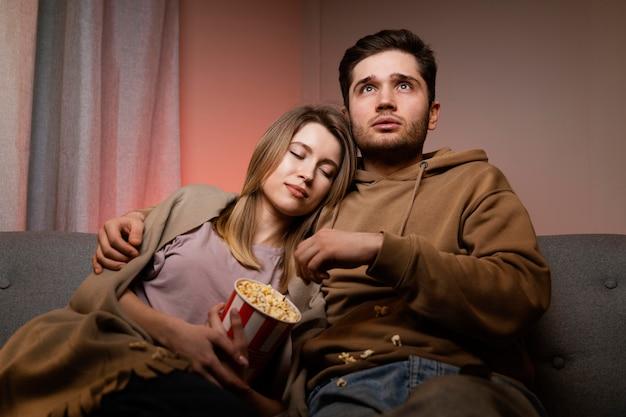 Coppia guardare la tv e mangiare popcorn Foto Gratuite