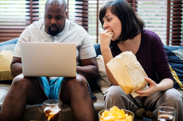 Пара смотрит телевизор на диване Premium Фотографии