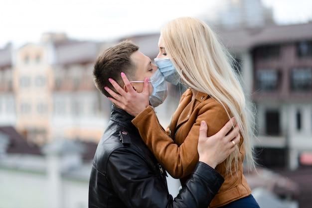 通りを歩きながらフェイスマスクを着ているカップル Premium写真