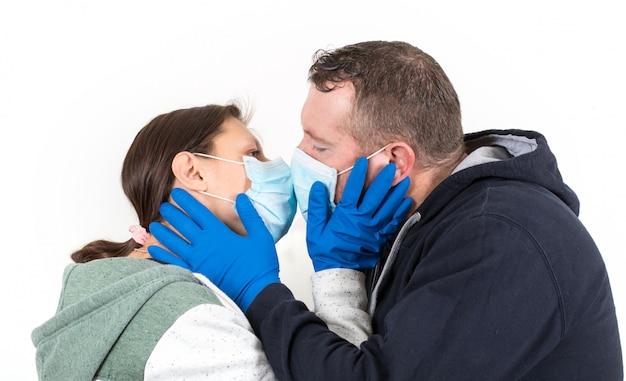 コロナウイルスのコンセプトにキスウイルスマスクを身に着けているカップル Premium写真