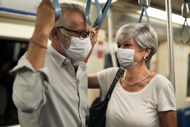 Couple wearing masks in train in the new normal Free Photo