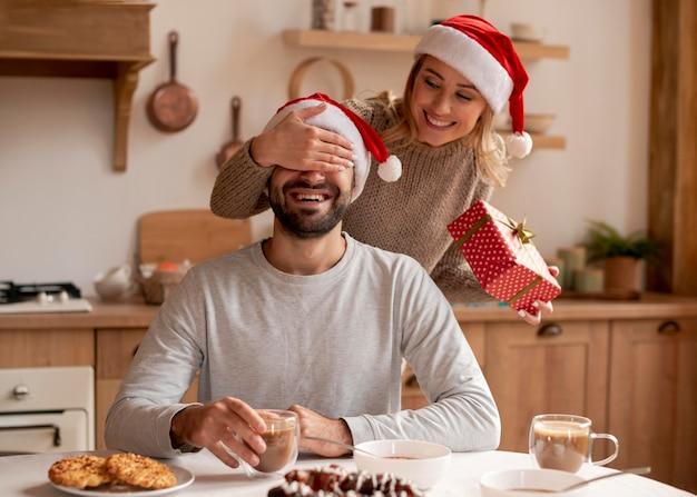 Пара в шляпах санта-клауса в помещении Бесплатные Фотографии