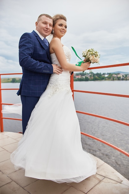 Couple wed embrace and kiss next houses near water Premium Photo