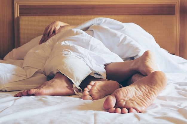 Couple on white bed in hotel room focus at feet Free Photo