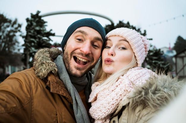 Coppia in inverno che soffia un bacio Foto Gratuite