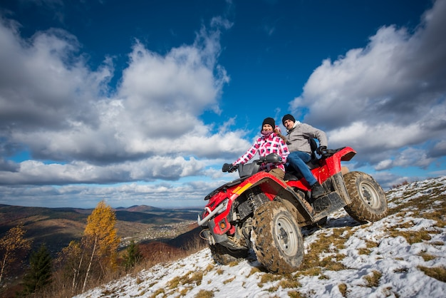 Couple in winter clothes riding on a red atv on a mountain slope Premium Photo
