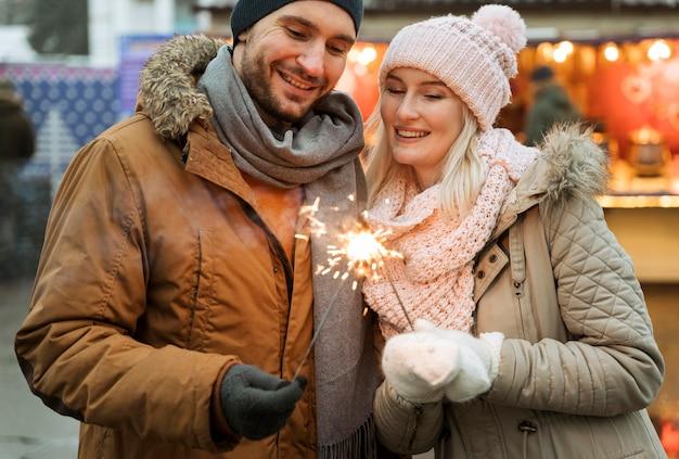 Coppia in inverno donna con fuochi d'artificio scintilla Foto Gratuite