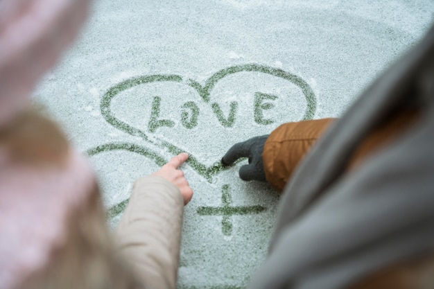 Couple in winter writing love in the snow Free Photo