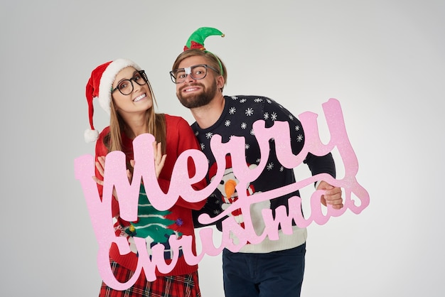 Couple wishing merry christmas to all Free Photo