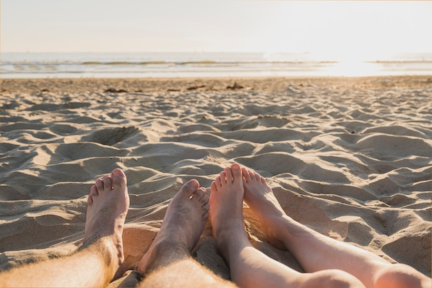Couple with bare feet on sand and sunset Free Photo