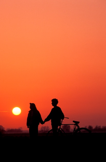 Couple with bicycle holding hands silhouetted against sunset sky Premium Photo