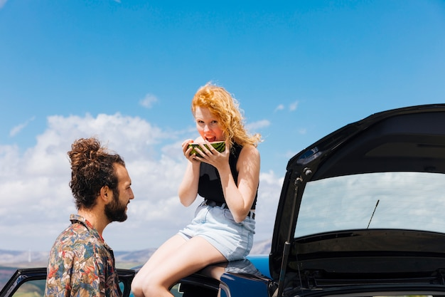 Couple with car eating watermelon outdoors Free Photo