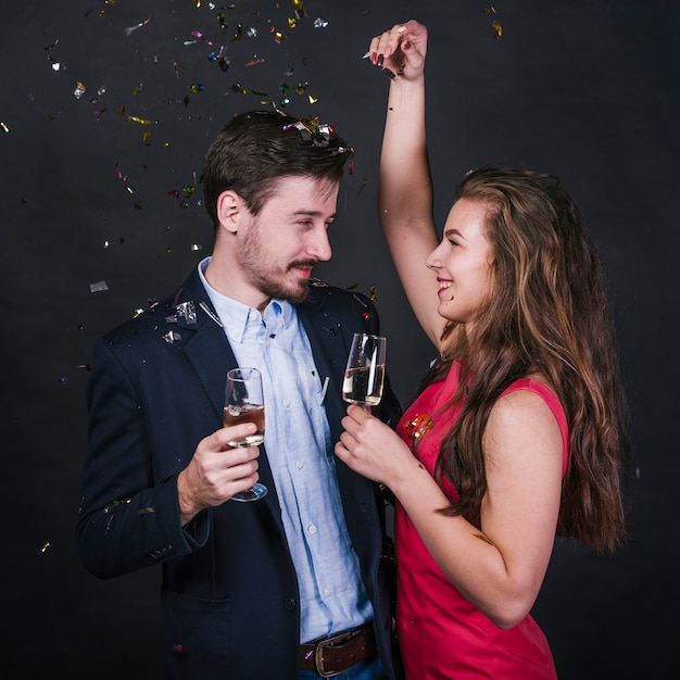 Couple with champagne glasses under spangles Free Photo