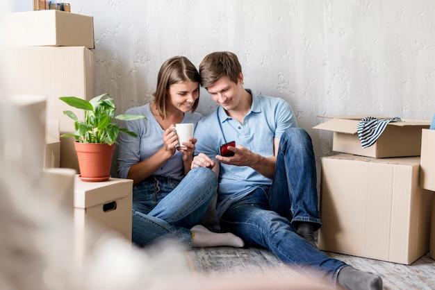 Пара с кофе и смартфоном, собирая вещи, чтобы переехать Бесплатные Фотографии