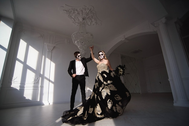 Couple with dark skull makeup on white background. halloween Premium Photo