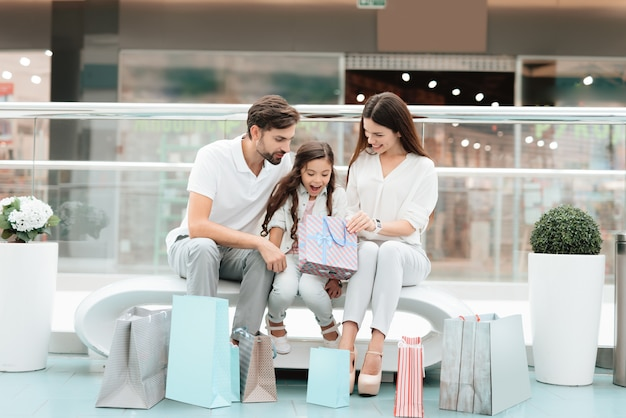 Couple with daughter with shopping bags are sitting on bench Premium Photo