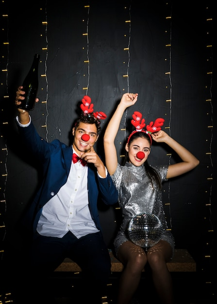 Couple with deer antlers headbands and funny noses with disco ball and bottle Free Photo