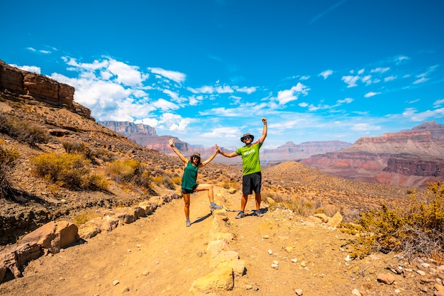 A couple with green shirt resting on the south kaibab trailhead trekking. grand canyon Premium Photo