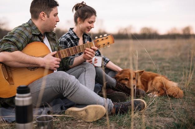 ギターとペットをカップルします。 無料写真
