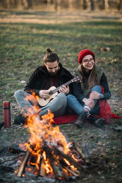 キャンプファイヤーの近くのギターとカップルします。 無料写真