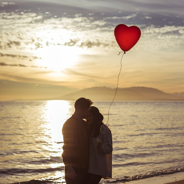 Couple with heart balloon hugging on sea shore in evening Free Photo