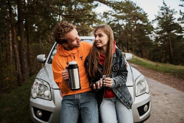 Пара с горячим напитком во время поездки Бесплатные Фотографии