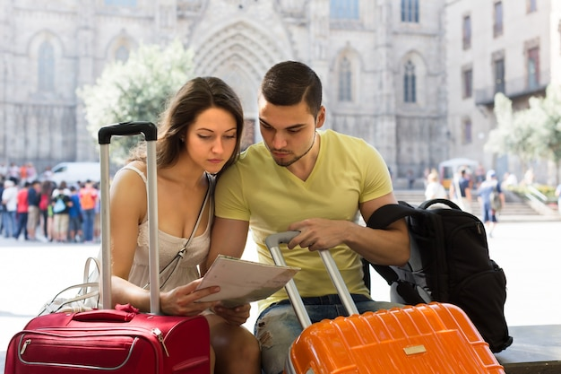 Couple with luggage reading map Free Photo